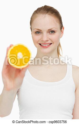 Woman holding an orange while smiling - csp9603756