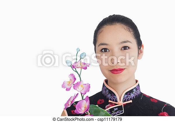 Woman holding an orchid while smiling  - csp11179179