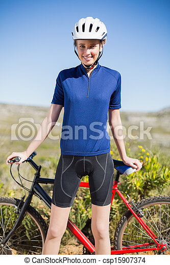 Woman holding and standing in front of bike - csp15907374