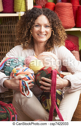 Woman Holding Balls Of Wool Sitting In Front Of Yarn Display - csp7422033