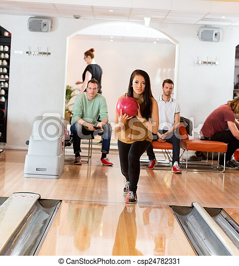 Woman Holding Bowling Ball in Club - csp24782331