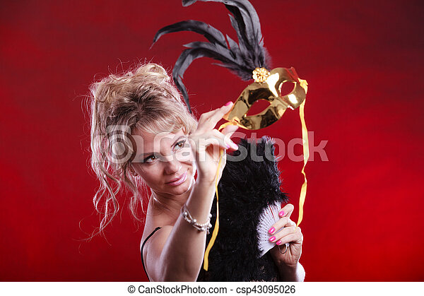 Woman holding carnival mask feather fan in hand - csp43095026