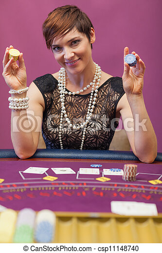 Woman holding chips in her hand in a casino - csp11148740