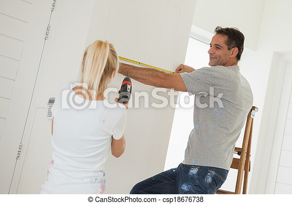 Woman holding drill while man measuring wall - csp18676738