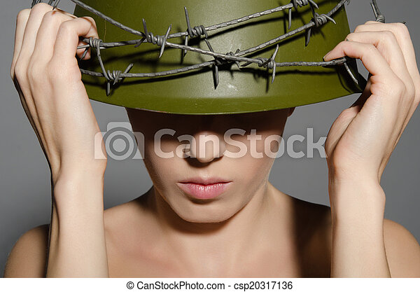 Woman holding hands military helmet with barbed wire - csp20317136