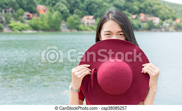 Woman holding hat standing in front of a lake - csp38085257