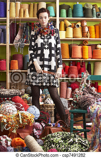 Woman Holding Knitting Needles Standing In Front Of Yarn Display - csp7491282