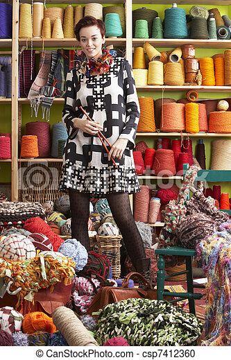 Woman Holding Knitting Needles Standing In Front Of Yarn Display - csp7412360
