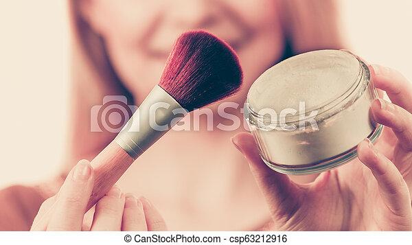 Woman holding make up brush - csp63212916