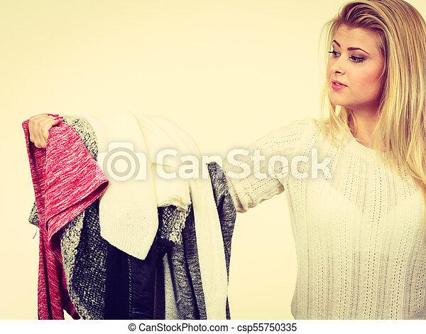 Woman holding many clothing - csp55750335