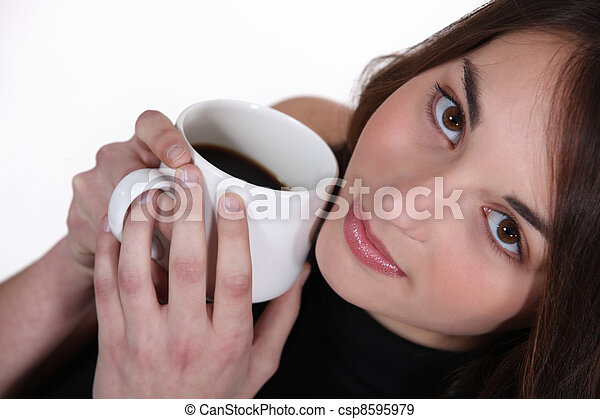 Woman holding mug of coffee to face - csp8595979