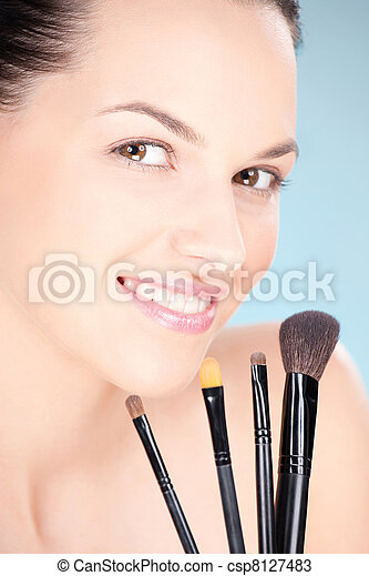 woman holding set of make up brushes - csp8127483