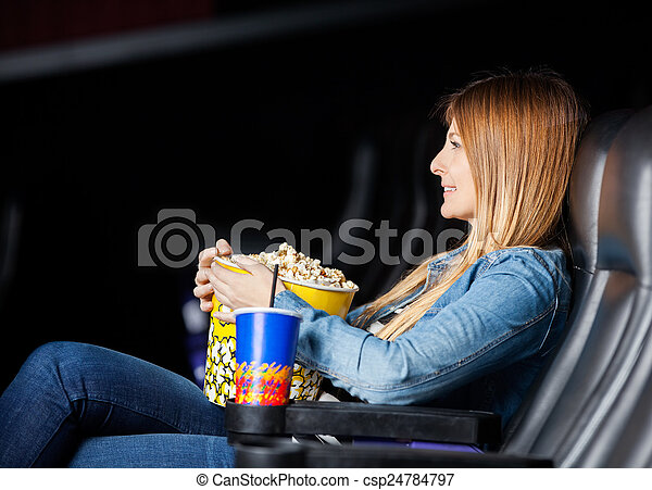 Woman Holding Snacks While Watching Movie At Theater - csp24784797