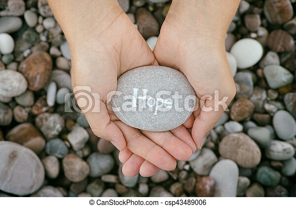 Woman holding stone with the word Hope in her palms - csp43489006