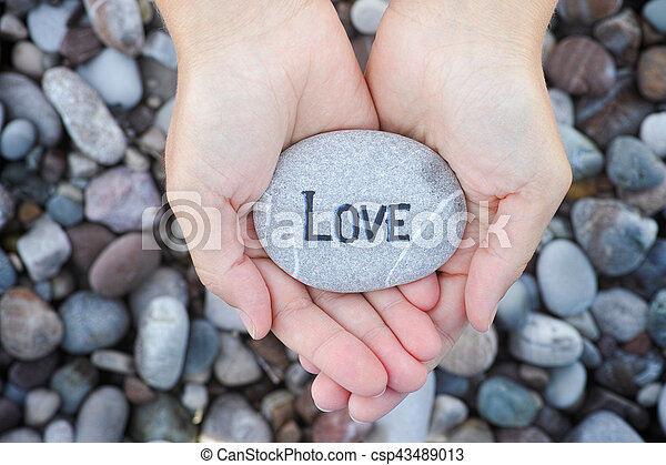 Woman holding stone with the word Love in her palms - csp43489013
