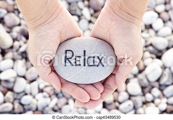 Woman holding stone with the word Relax in her palms - csp43489530