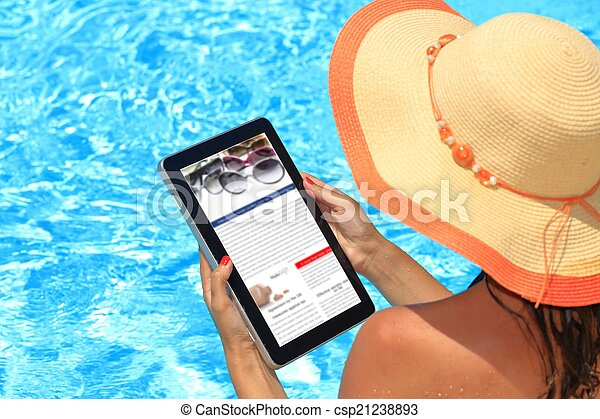 Woman holding tablet computer in the pool - csp21238893