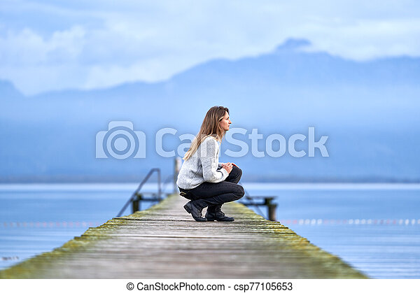 Woman in a jetty facing the lake - csp77105653