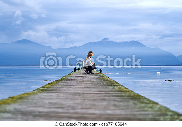 Woman in a jetty facing the lake - csp77105644