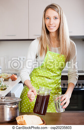 Woman in apron pouring brown beverage into glass   - csp20235603