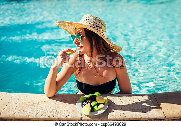 Woman in bikini eating fruits and relaxing in swimming pool. All inclusive. Summer vacation - csp66493629
