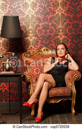 Woman In Black Dress Sitting On A Vintage Chair And Looks