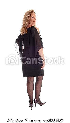 Woman in black dress standing from back. - csp35654627