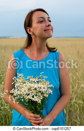woman in blue dress with chamomiles - csp6101257