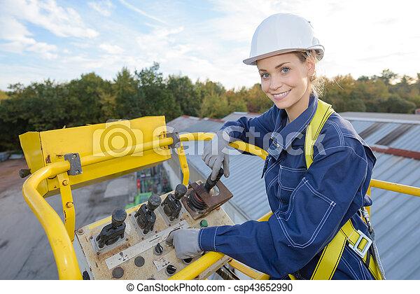 Woman in bucket of cherry picker - csp43652990