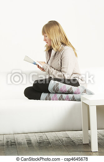 Woman in cardigan reading book sideview - csp4645678