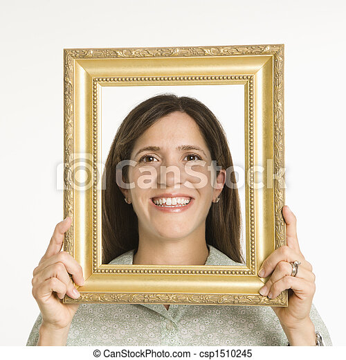 Woman in frame. Woman holding frame in front of face smiling.