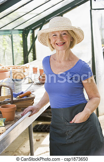 Woman in greenhouse smiling - csp1873650