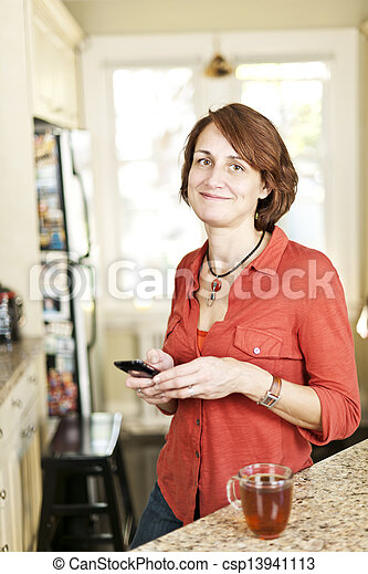 Woman in kitchen with cell phone - csp13941113