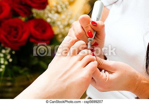 Woman in nail studio receiving pedicure - csp5699207