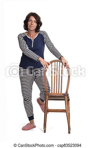 woman in pajamas playing with a chair on white background,  the knee above the chair - csp83523094
