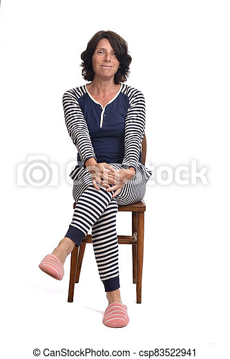 woman in pajamas sitting o a chair on white background - csp83522941