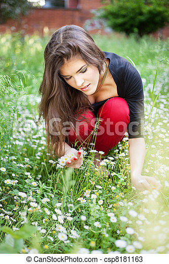 woman in park gather spring flowers - csp8181163