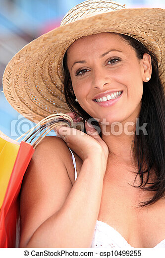 Woman in straw hat holding shopping bags - csp10499255