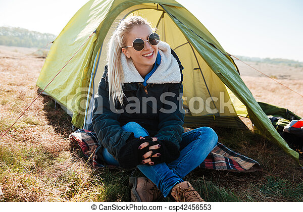 Woman in sunglasses and boots sitting near tent at campsite - csp42456553