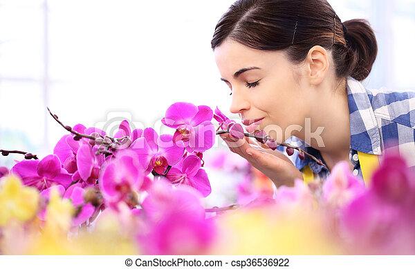 woman in the garden of flowers, touches and smells an orchid - csp36536922