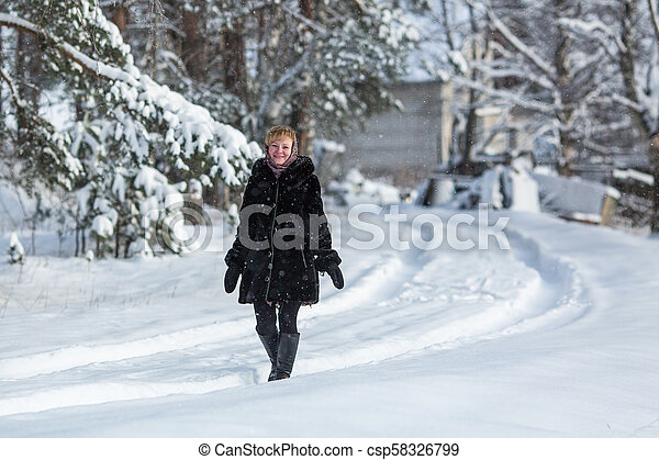 Woman in the snowy russian village at winter. - csp58326799