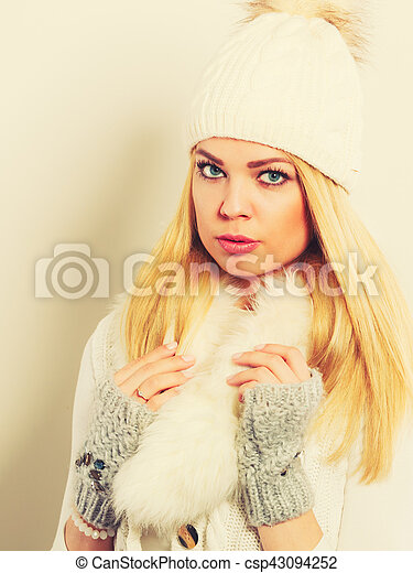 Woman in winter clothes woolen cap fur scarf - csp43094252