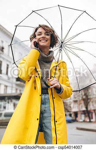 4142a5382 Woman In Yellow Raincoat And Glasses Talking On Mobile Phone Holding Big  Umbrella While Strolling