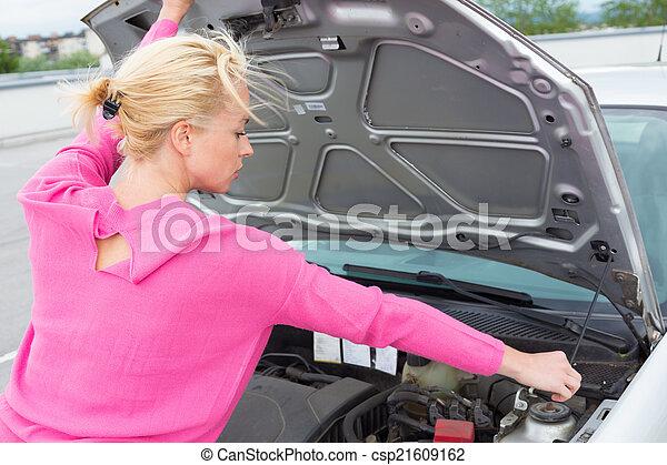 Woman inspecting broken car engine. - csp21609162