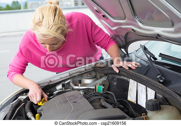 Woman inspecting broken car engine. - csp21609156