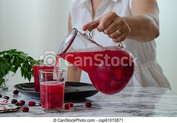 Woman is filling cranberry juice in glass. - csp61015871