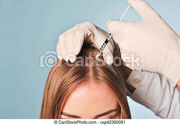woman is getting injection in head. Mesotherapy. - csp42360091