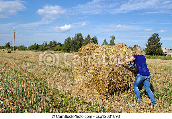 woman jeans move push straw bale agriculture field  - csp12631893
