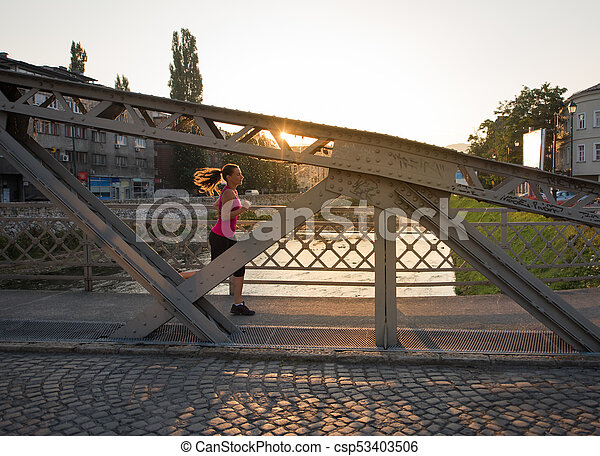 woman jogging across the bridge at sunny morning - csp53403506