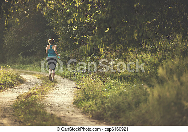 woman jogging along a country road - csp61609211